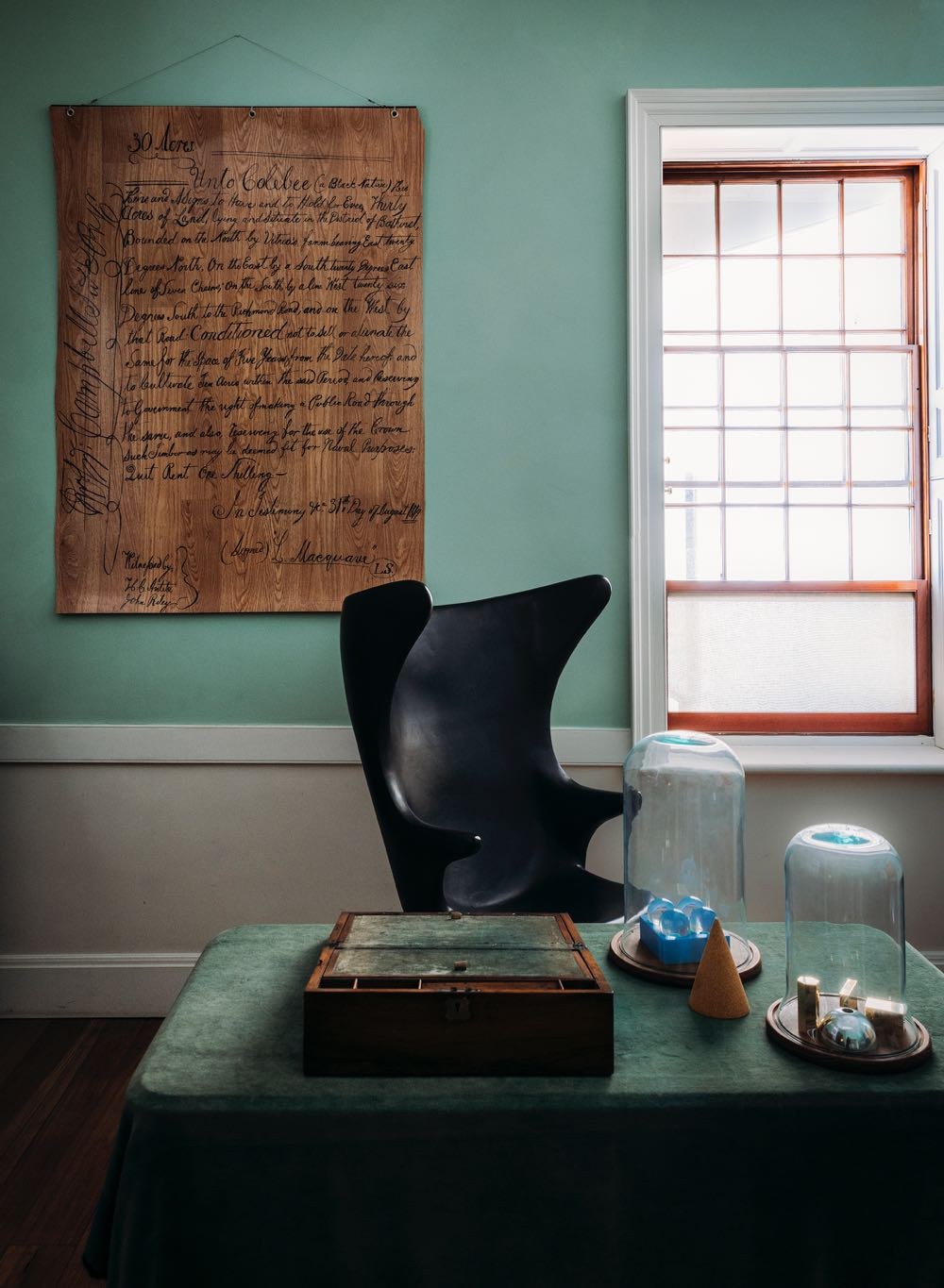 The 'Carbon Wingback' chair by Sarah King (made by Ben Blakebrough) in Governor Macquarie's study. The wall art is a replica of a document from 1819 recording the first land grant by Governor Macquarie to an Aboriginal  The artwork is handwritten in laundry marker on floorboard style linoleum by Joan Ross (2006). Objects under the cloche are by Daniel Emma.