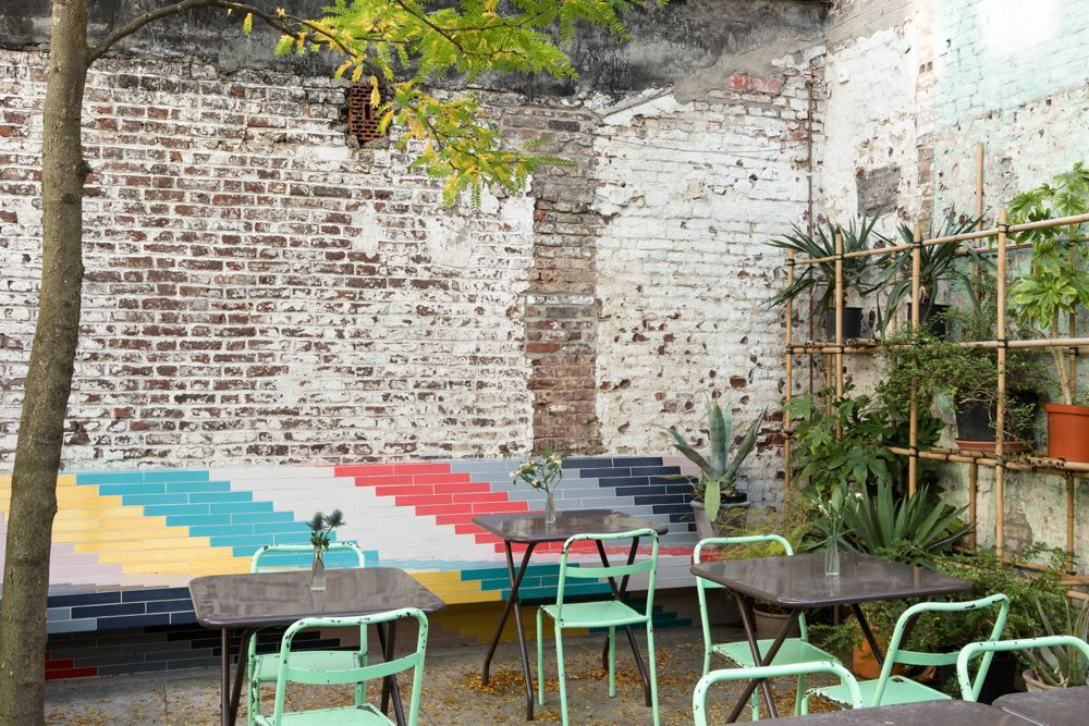 The garden courtyard of the cafe features a mammoth tiled banquette that continues into the cafe's interior. The tiles used are by Danish brand  File Under Pop and are available for sale in the Clouds9000 shop.