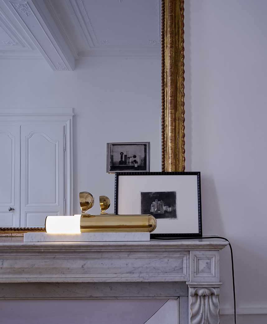 The ISP lamp by Ilia Potemine in table mode. The brass tube sits on top of a carved marble slab while the glass tube slides out and acts a a physical dimmer - the further out of the brass tube the user slides it,  the brighter it becomes.