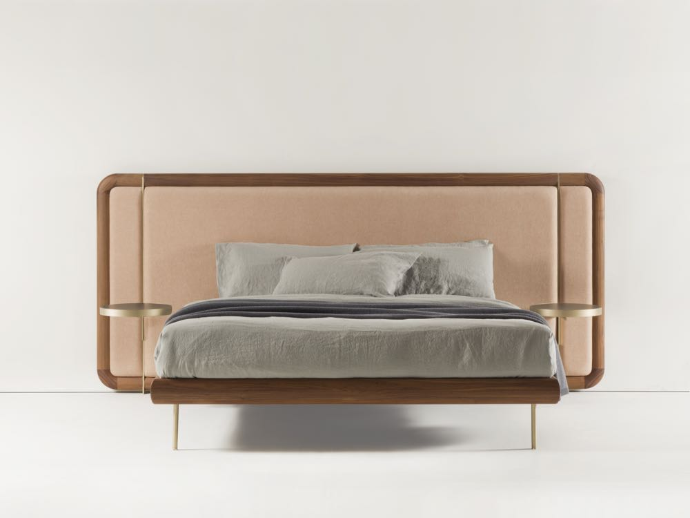 The 'Killian' bed by Marconato and Zappa for  Porada  features integrated brass bedside tables. The bed frame is in Canaletta walnut with an upholstered bedhead and brass feet.