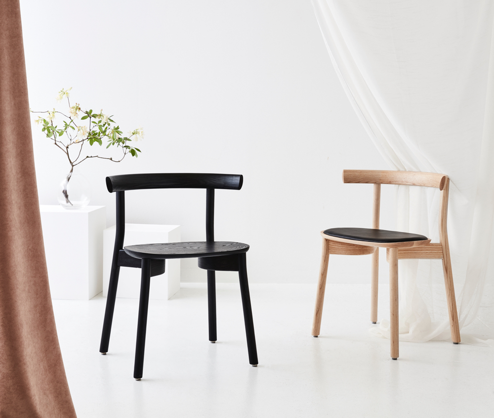 The 'Torii' chair by Chris Nicholson for Dessein Furniture shown here in black stained ash (left) and natural ash with upholstered leather seat (right).