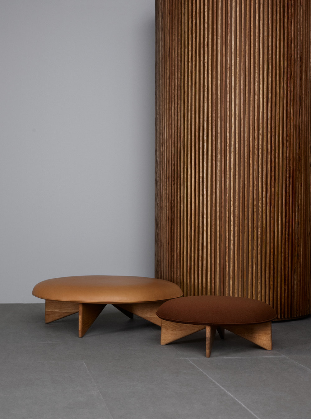 The Fogia 'Utility' pouf features a strong rocket fin motif in the base but this fifties look is tempered by the use of solid wood and soft mushroom-shaped upholstery.