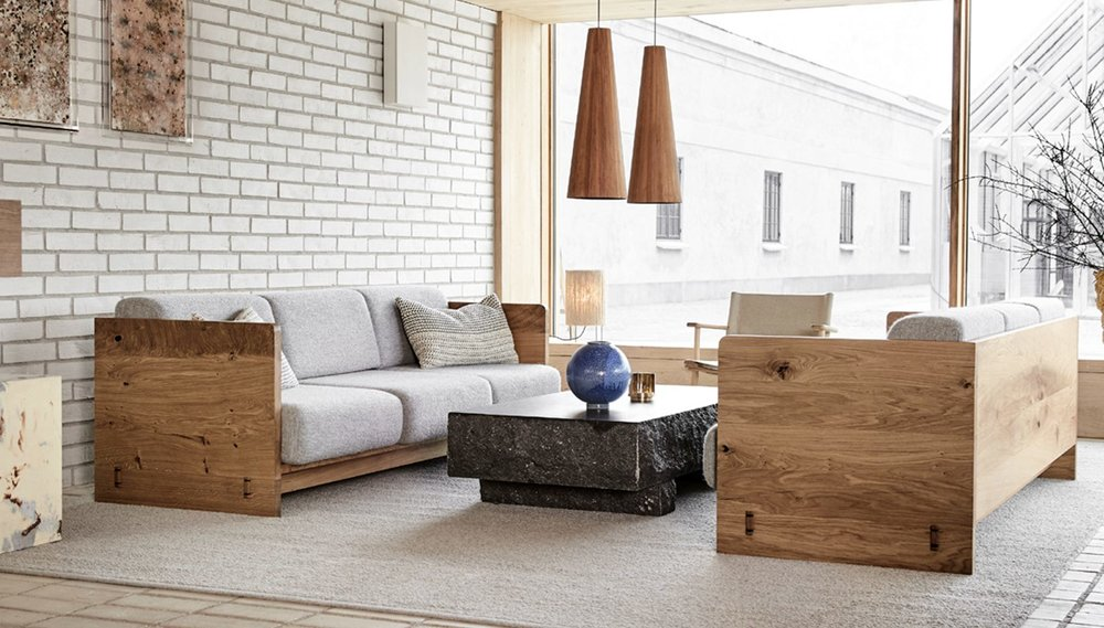 The 'Karm' sofa by Studio David Thulstrup is constructed in solid oak with visible square peg detailing on the sides where the base and side panels meet.