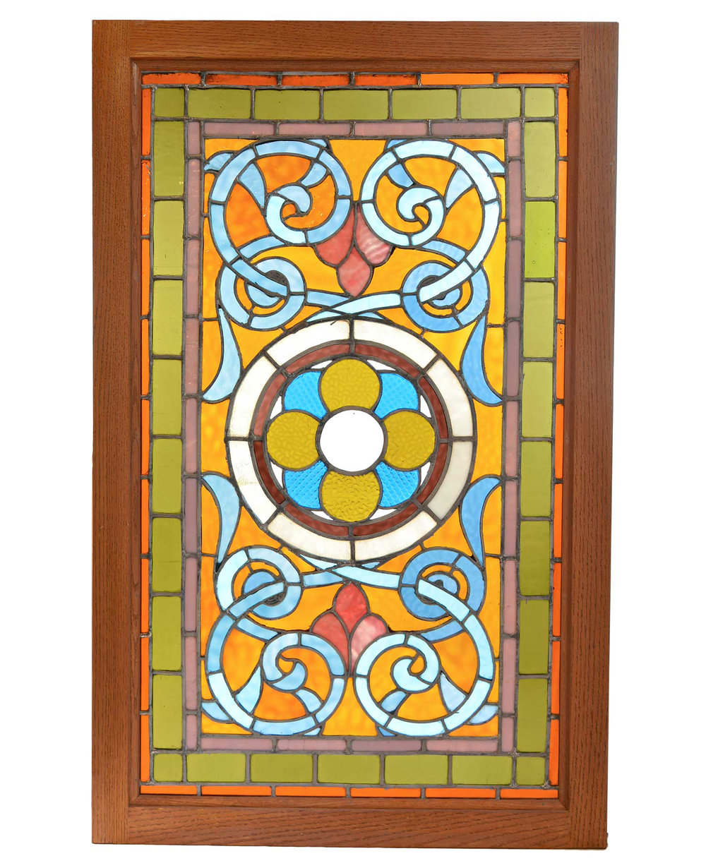 amber and teal victorian window with a roundel