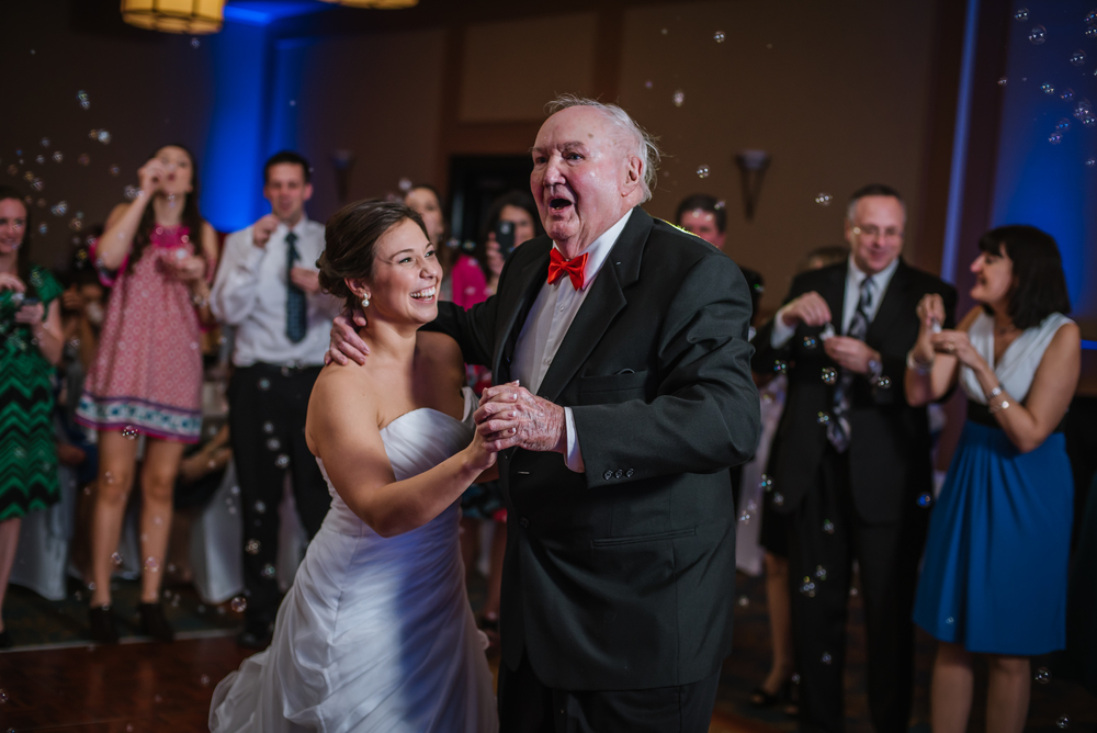 "This is still my favorite reception moment of all time! Bride Lisa danced to ""Tiny Bubbles"" with her Grandpa as her family blew bubbles! He loved it so much!"