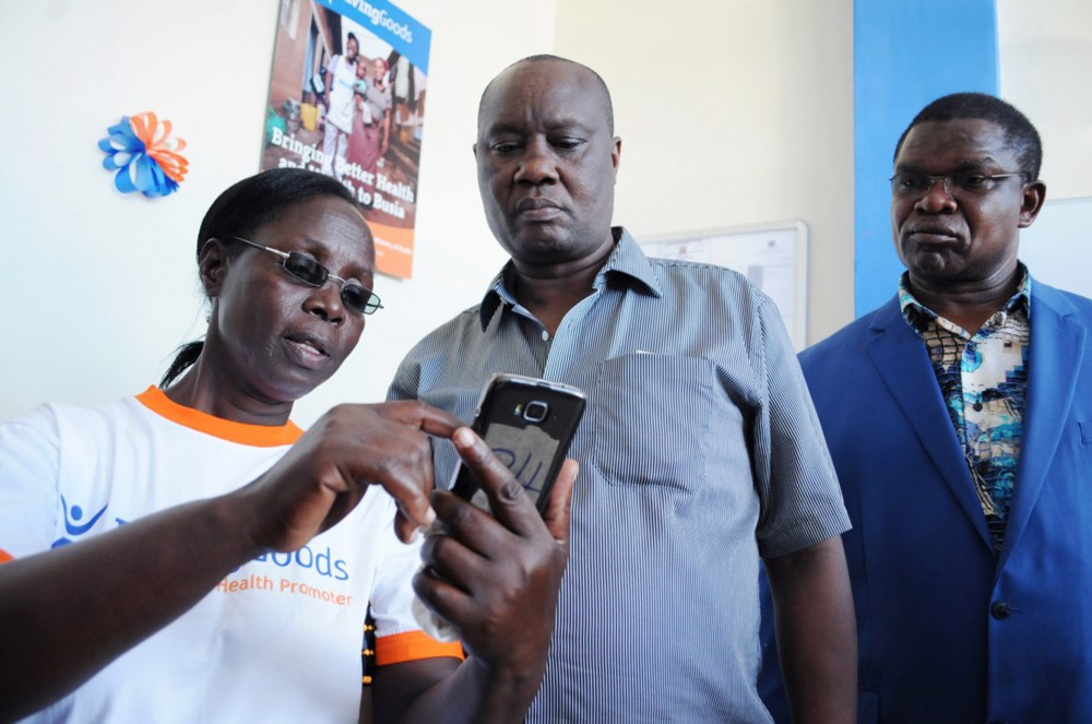 Monica shows off her Android phone to the Busia Governor and Health Minister. The phone does guided health assessments, registration and more.