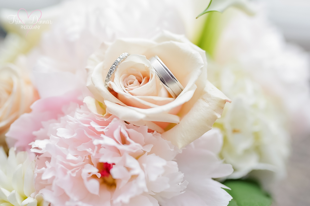 Photograph of wedding bands in bridal bouquet in Maine