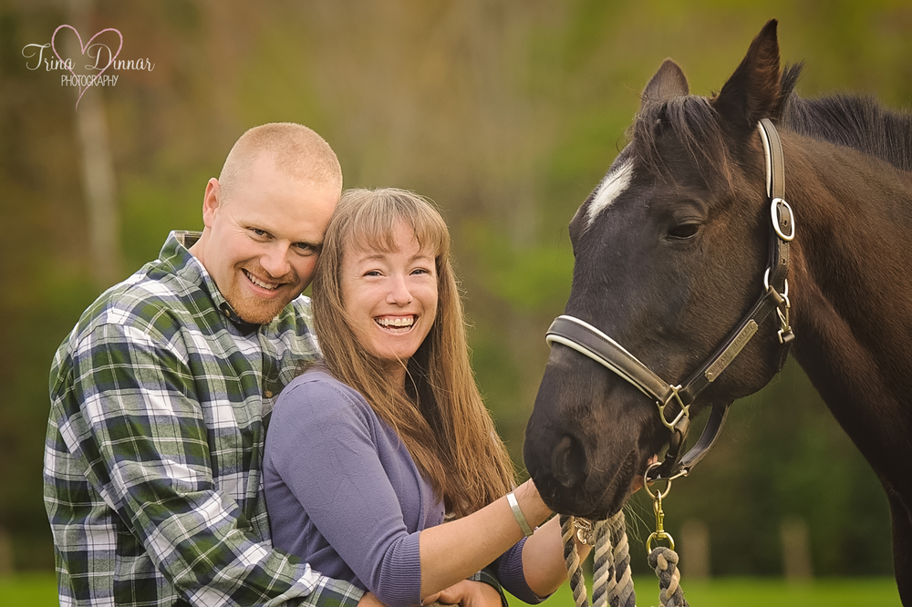 Maine engagement photography in West Baldwin. The couple poses with their horse on the farm.