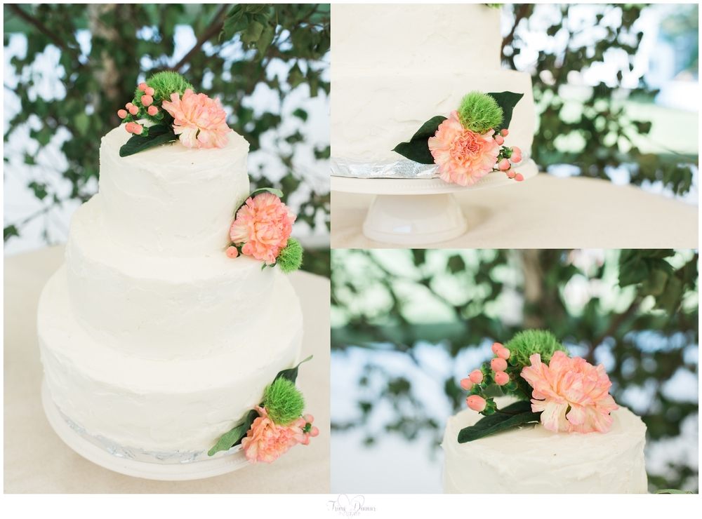 Three tier wedding cake with peach flowers.