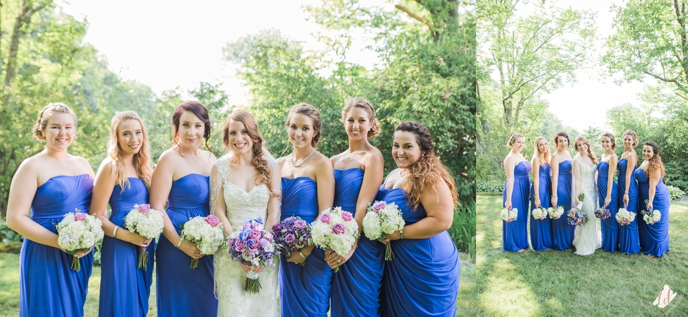 Bridesmaids wearing blue dresses with purple and violet flowers.