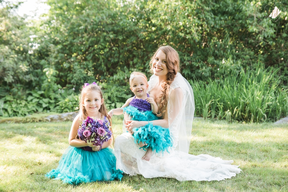 Bride poses with her two flower girls wearing blue, purple and teal wedding colors.