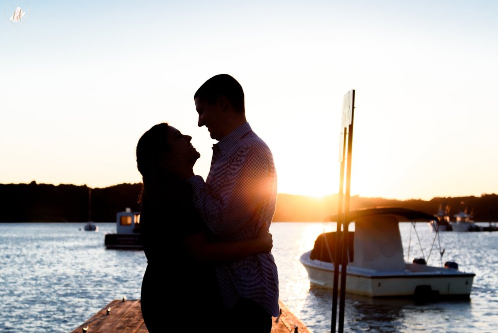 A couple's silhouette at a Maine beach harbor.