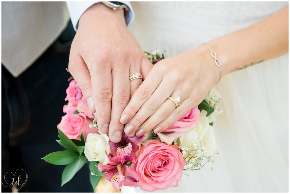 Wedding Rings on Hands over Bouquet