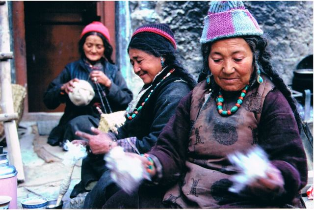 Women in Miktong, Skurbuchan working on wool together: hand-prepping, spinning, and winding a two-stranded ball.