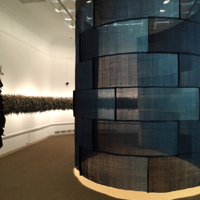 Rowland Ricketts' installation piece: dried indigo plants hang along the wall, and a pieced work of dyed plant fiber created a cylindrical space in the center of the room. There is also a soundtrack playing, which is derived from aspects of the indigo processing.