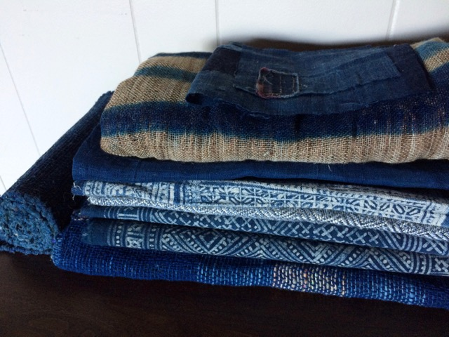 Hmong batik cloths in the middle of the pile, interspersed with Japanese fabrics and my own weaving at the bottom.