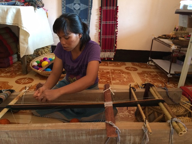 Mone begins the warp, directly onto the loom bars which are supported on a frame. The string heddles are added as the warp is wound (whits strings wrapped around the sword beater in the middle of the photo.)