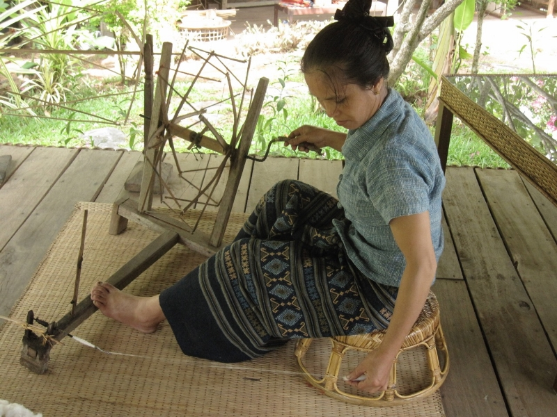 Lao woman spinning cotton, 2013. Her clothing is made from handspun cotton.
