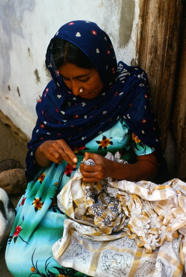 1995 photo of a woman in Mandvi, Gujarat, tying a silk sari for resist dyeing, called bandhani