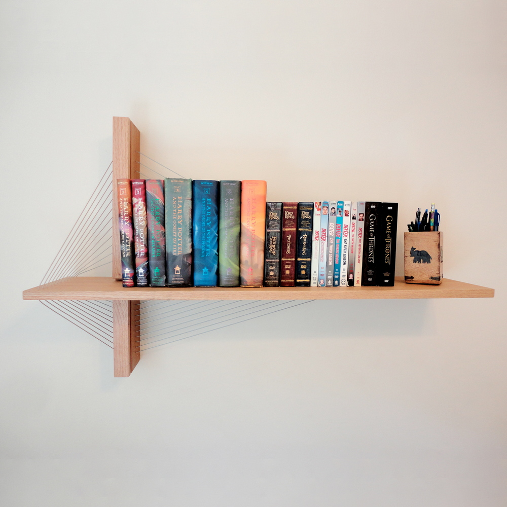 Suspemsion shelf by robby cuthbert. A modern sculptural shelf made of mahogany, red oak and steel cable. Architecturally inspired and built with an engineering mindset. Suspension bridges were a big inspiration for this design as steel cables are used to support the cantilevered shelf.