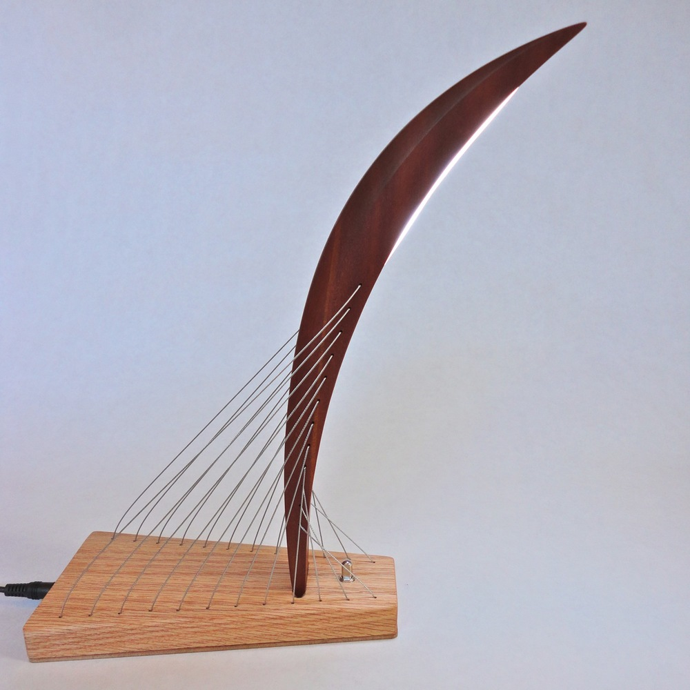 A modern sculpture LED lamp. Steel cables under tension keep the central mahogany curve balanced atop the red oak base.