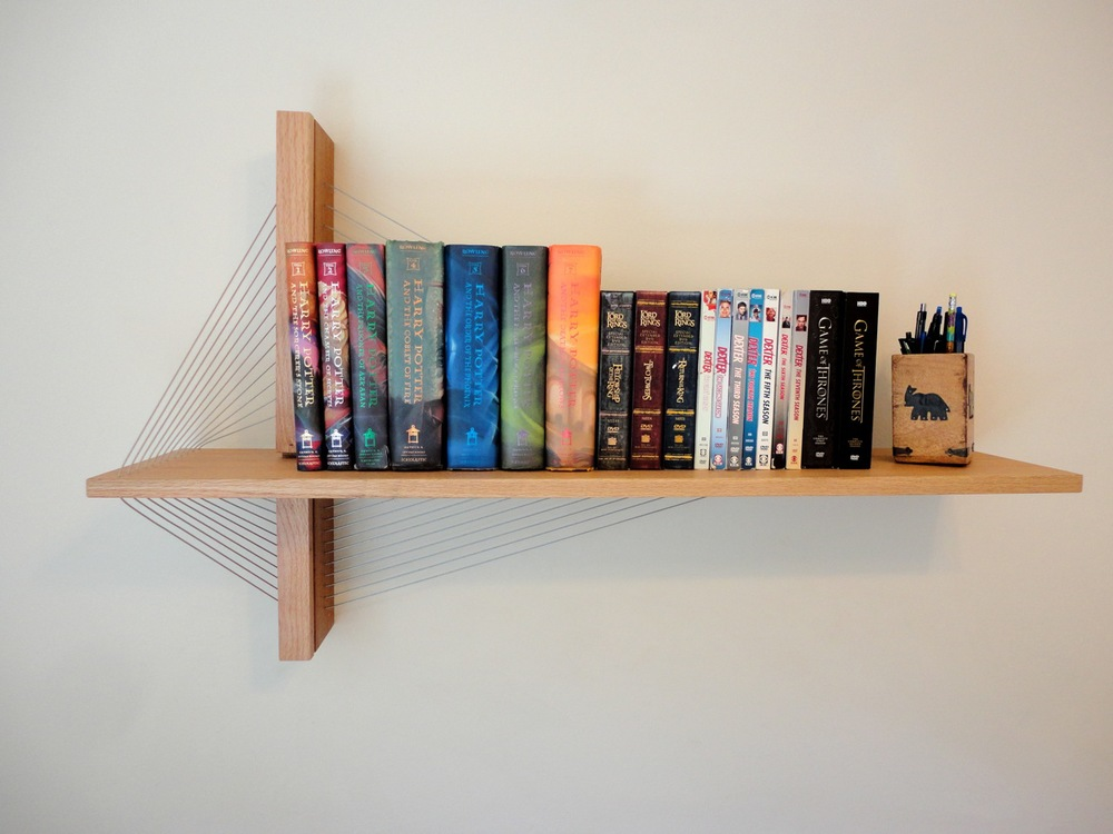 "A modern sculptural ""floating"" shelf by Robby Cuthbert. Inspired by suspension bridges, this shelf is carefully engineered out of mahogany and red oak. The vertical fin mounts to the wall and the horizontal shelf is cantilevered out and supported by steel cables under tension."
