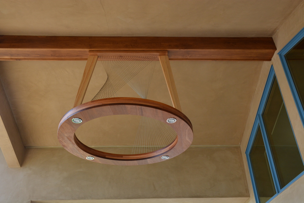 Ring light by Robby Cuthbert. A mourn LED lighting fixture with mahogany, oak and steel cable