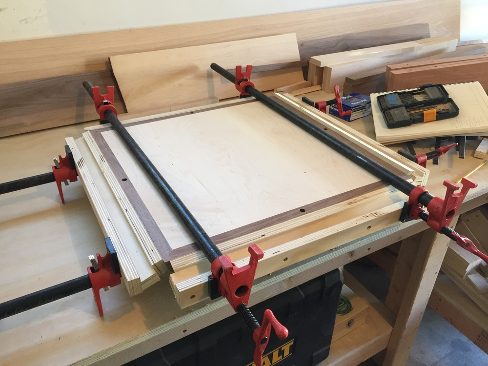 I wanted the maple tabletop to be perfectly framed by a thin walnut strip. The angled edges made this tricky to accomplish, so I had to build a jig to get everything set just right.