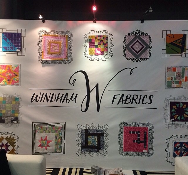 A close up of the booth wall featuring the redesigned logo and my doodle frame (right above the word Windham) Photo courtesy of @windhamfabrics on Instagram.