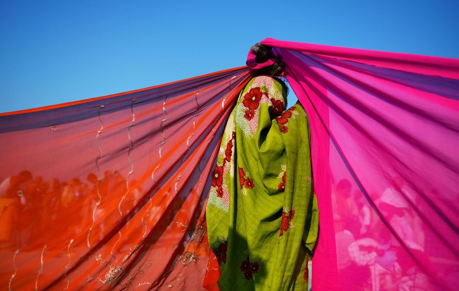 A women with her back to camera holding up fabric, India. (R. Schmidt, Afp) <http://www.internazionale.it<