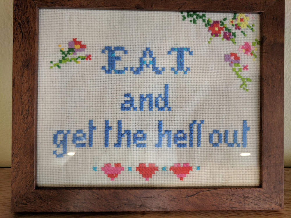 "Needlepoint above the bar advises, ""Eat and Get the Hell Out."""