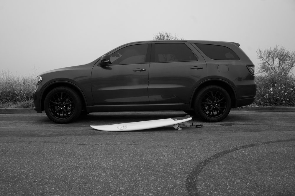 suv and a surfboard black and white photo