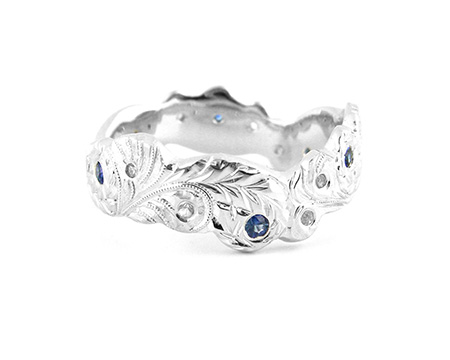 10k white gold, rhodium plated, white and blue sapphires  Contour wedding band, hand engraved with leaf and floral motifs. Client's design brought to life.