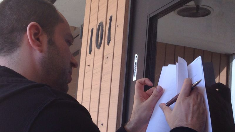 Jan Koum signs the $19 billion Facebook deal paperwork on the door of his old welfare office in Mountain View, Calif. (Photo courtesy of Jan Koum via Forbes)