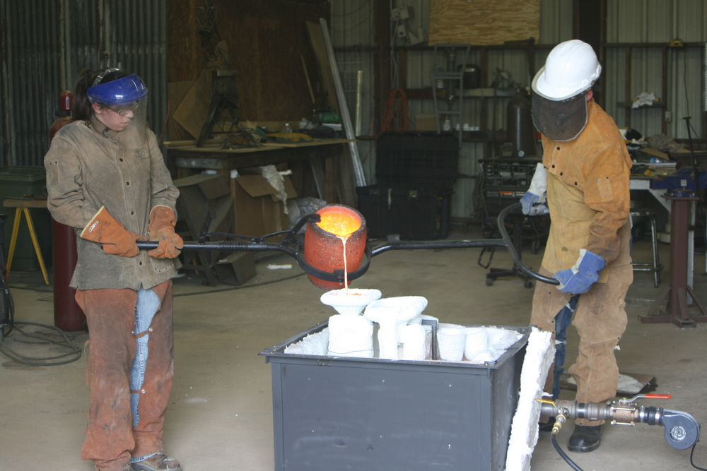 Jen and Adam (Jen's business partner and Fiancé) pouring bronze in the foundry section