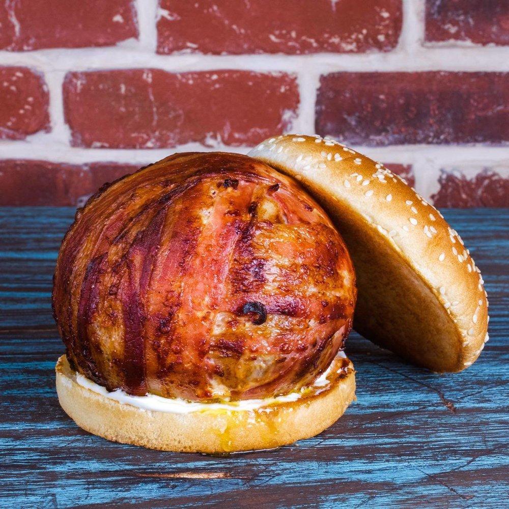 Royal Lucy - štedráporcia hovädzieho mäsa a cheddaru obalených v prémiovej slanine. Podávanés Jack Daniel's BBQ omáčkou.