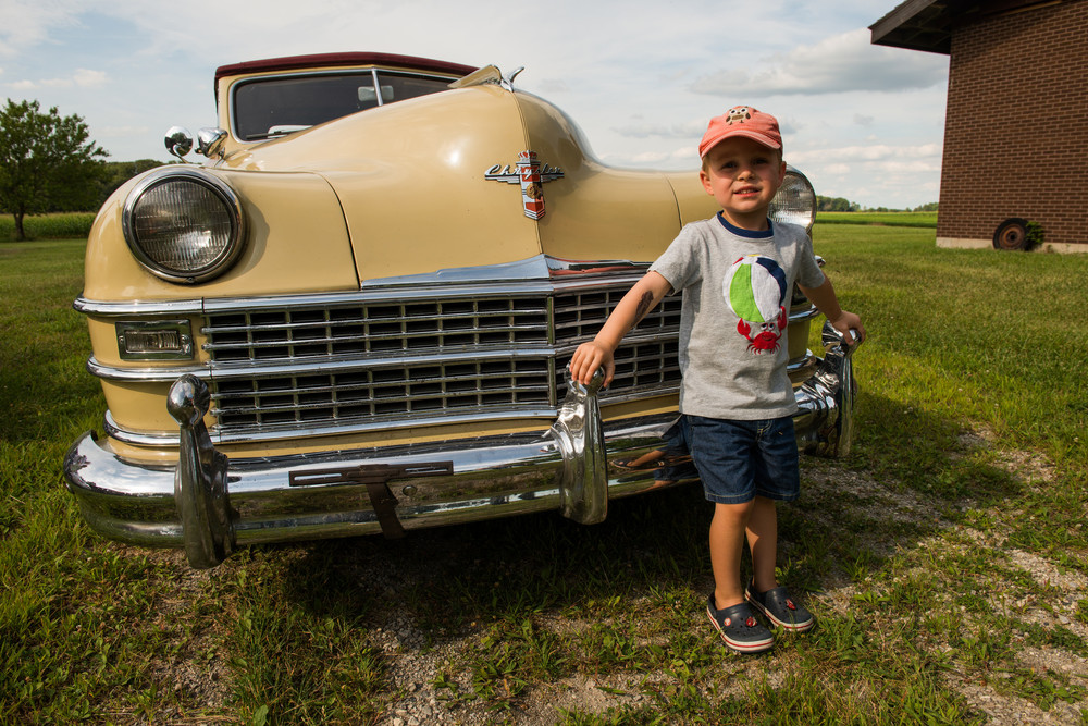 Oliver posing with my grandfather's prized 1947 Chrysler Town and Country convertible outside his boyhood home - August 2015