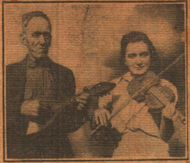 T.E. Hixson holding a mandolin made from a gourd; his daughter Opal Hixson holds the match stick fiddle.