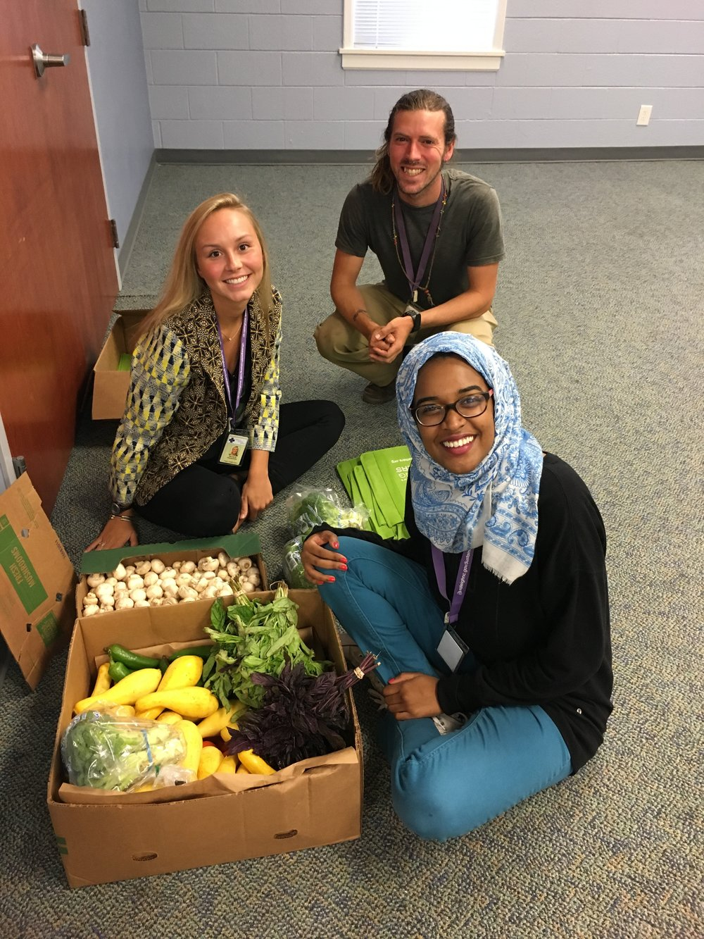 L to R: Natalie Holdstock, Garden & Wellness Coordinator Jesse Crouch, and Doha Medani helping fill bags of produce for Cooking Matters participants to take home.