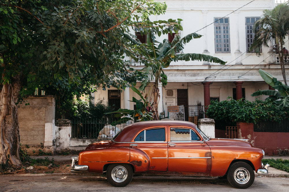 A classic orange 1950's car outside of a residence in a neighboorhood of Havana, Vedado in Cuba.
