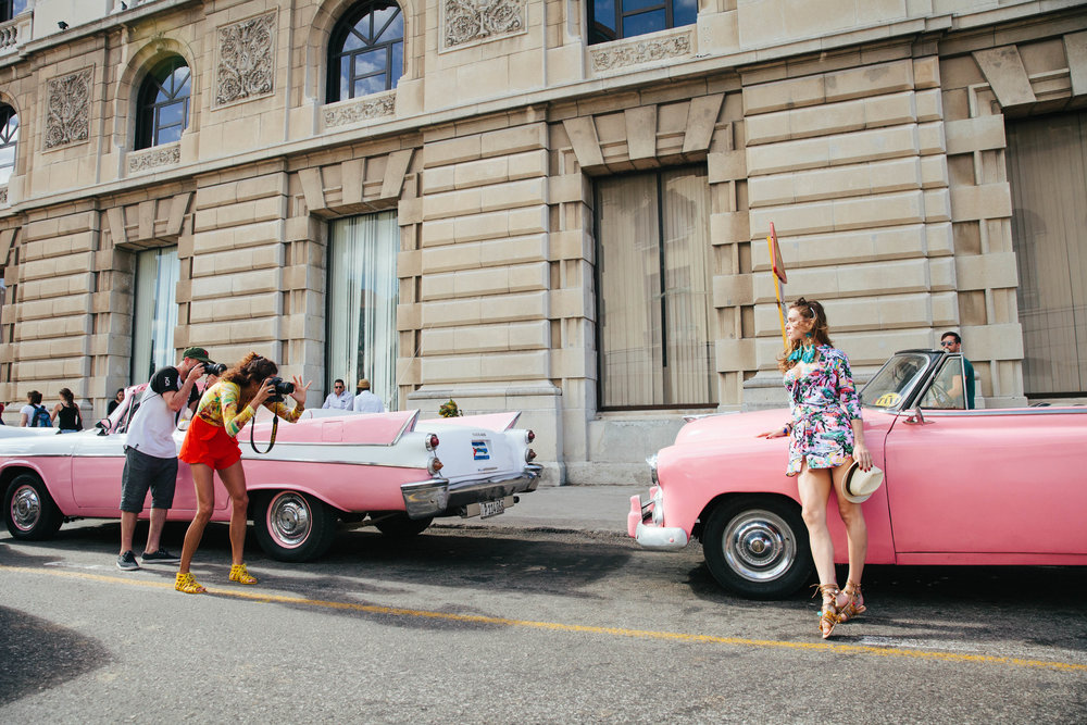 Photographers taking pictures of a model on a 1950's classic pink car in Havana, Cuba.