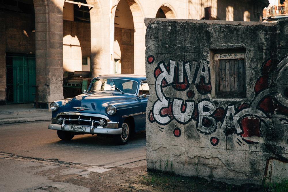 Viva Cuba written on a dilapidated wall in Havana, Cuba, with a blue classic car.