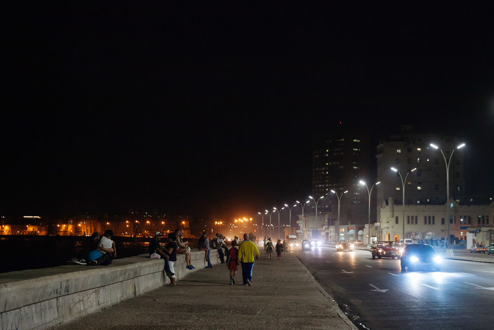 Locals and tourists walk the Malecon at night in Havana, Cuba.