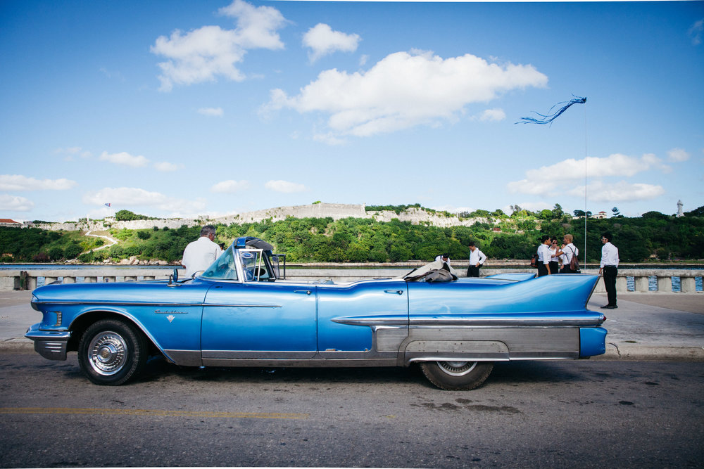 A newly refurbished classic car makes its way down the Malecon in Havana, Cuba.