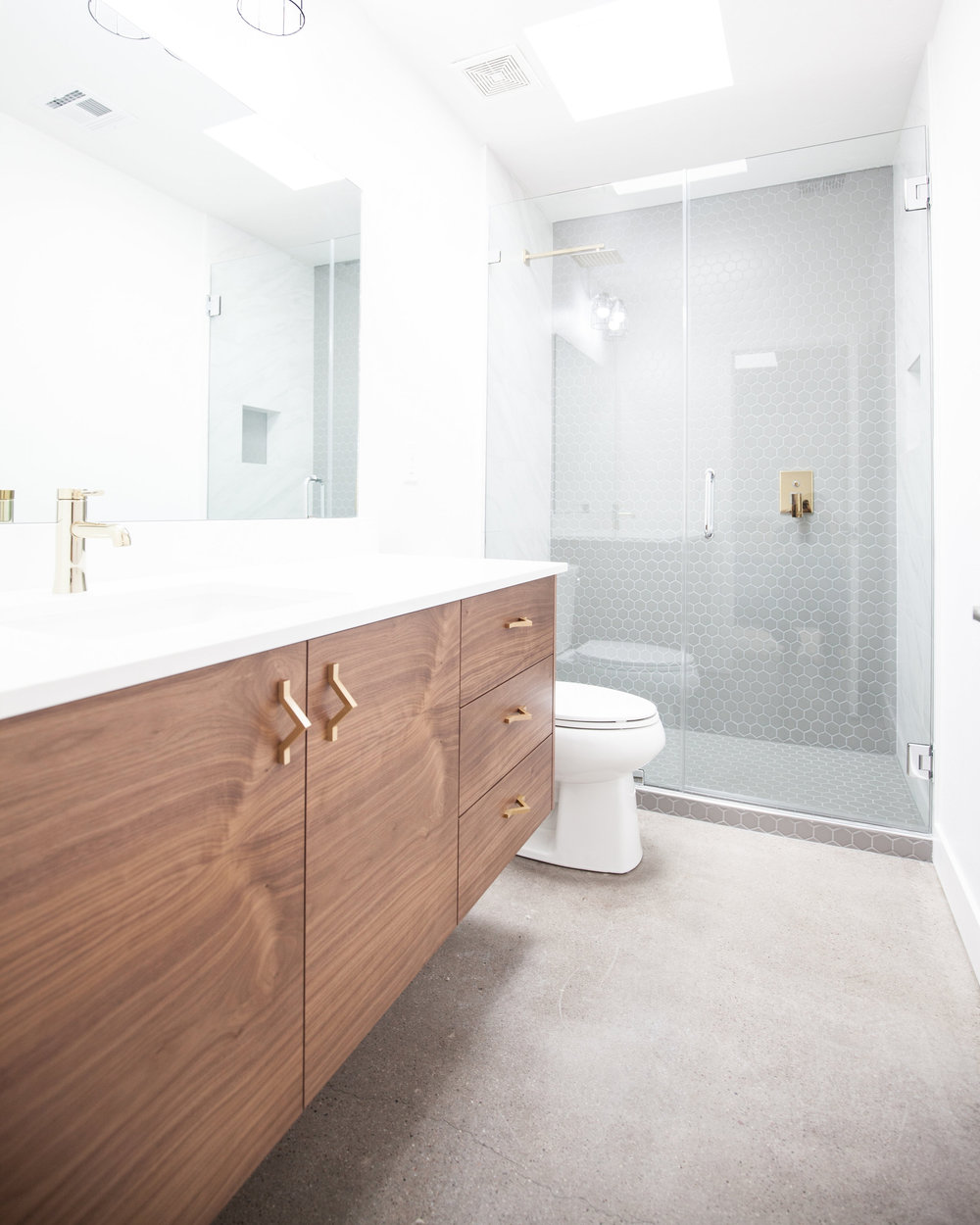 Modern Bathroom with Walnut Cabinetry and gold fixtures.