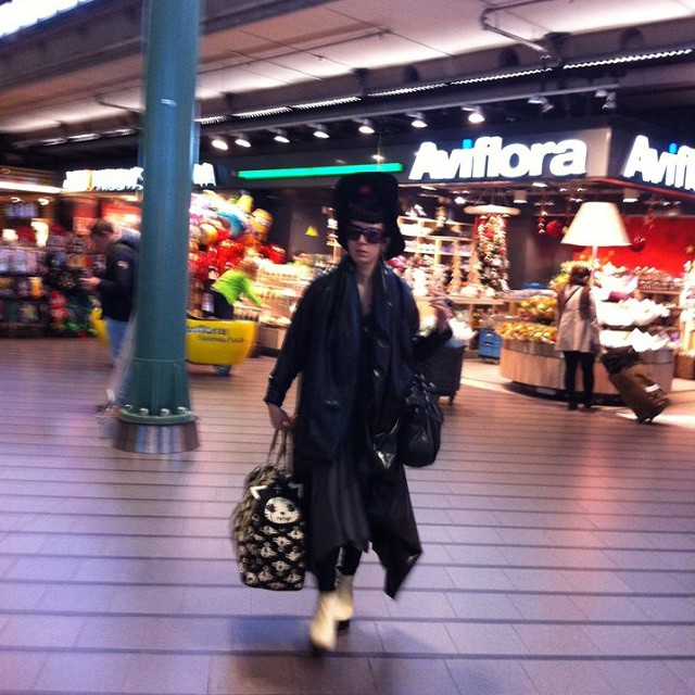 Traveling thru the airport in #Amsterdam. #ReneeMasoomian #latex winter coat, #viviennewestwood purse and overnight case, #unitednude wedges. #thisishowitravel