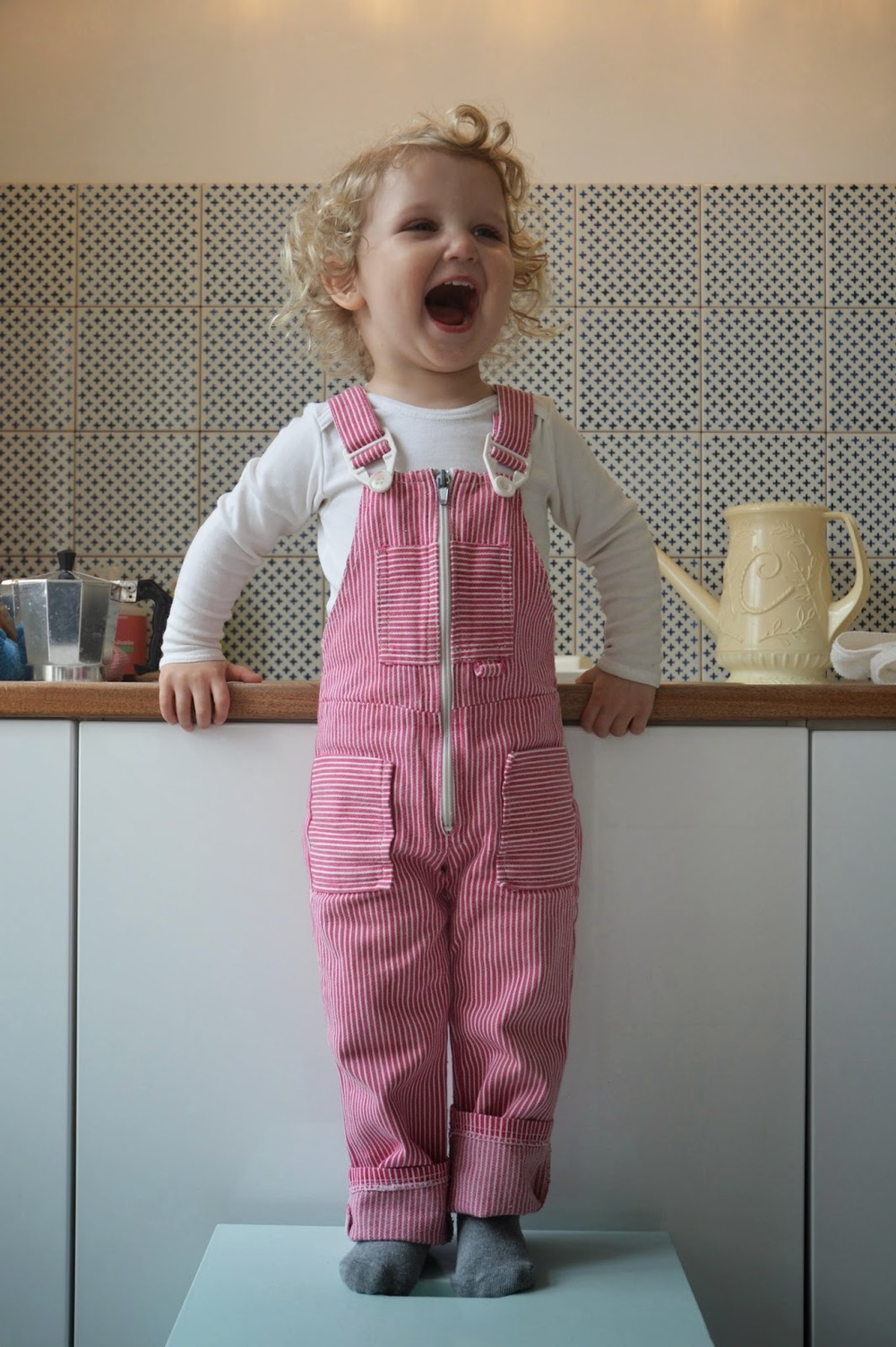 Quite happy with her new dungarees.