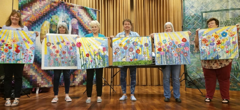 Members of the Nite Owl Quilters Guild showing off their Whimsical Garden quilts at their April 2018 meeting. Photo by Sharon Chaffino