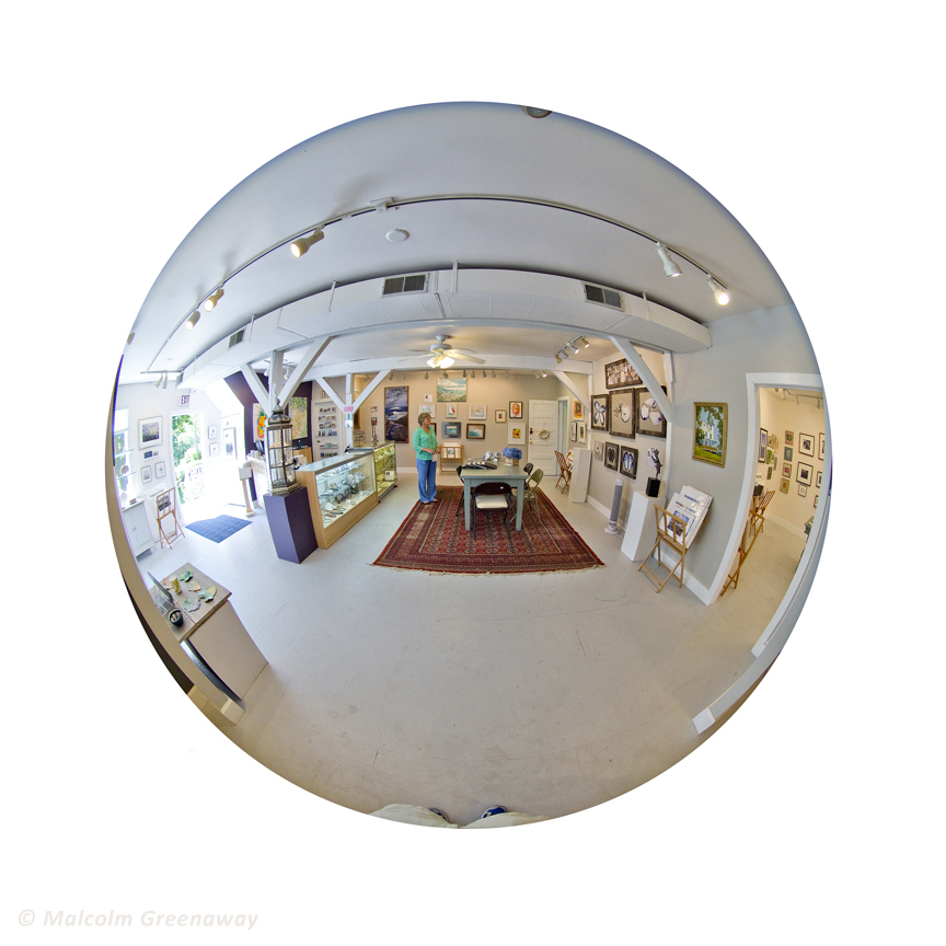 Here is the interior of the Spring Street Gallery.  My work can be seen in miniature, around the front door, but what you can really see is the rug.  That's my rug.  And, just to give you an idea of how a fish eye lens works, that odd little shape at the bottom of the picture is the bottom of Malcolm's legs and the top of his feet.
