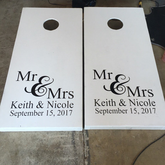 Cornhole board depicting wedding couple and wedding date